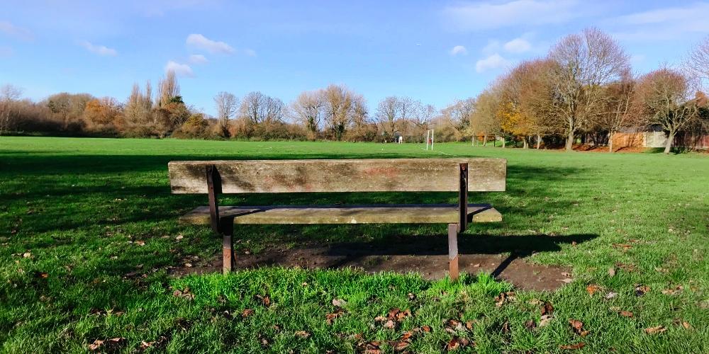 Park bench in Warren Avenue Playing Fields, Bromley, December 2020